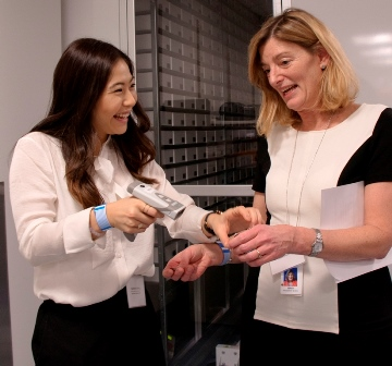 Katherine Wong of CST's Device team demonstrates patient wristband barcode scanning to Mary Ackenhusen, CEO of VCH